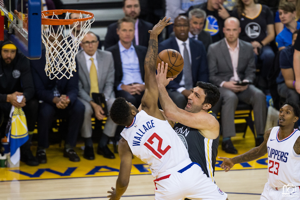 Golden State Warriors center Zaza Pachulia (27) is beat up by LA Clippers guard Tyrone Wallace (12) at the basket at Oracle Arena in Oakland, California, on February 22, 2018. (Stan Olszewski/Special to S.F. Examiner)