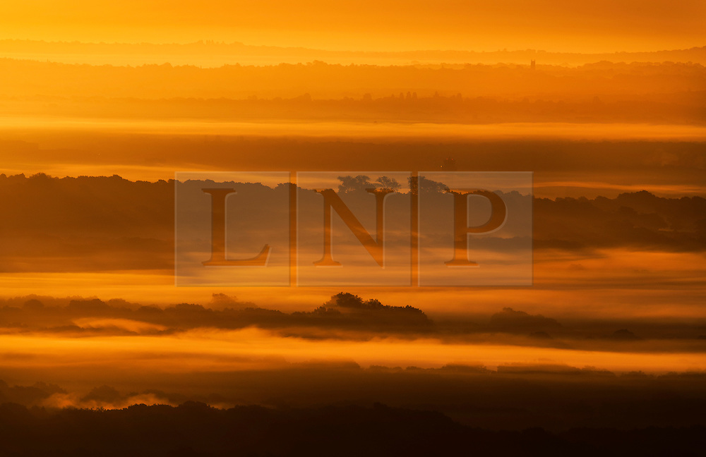 © Licensed to London News Pictures. 03/10/2016. Dorking, UK. Mist carpets the hills and valleys seen from near Leith Hill at dawn. Sunshine and warm autumn weather are forecast for today. Photo credit: Peter Macdiarmid/LNP
