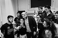 """NAPLES, ITALY - 30 JULY 2018: Roberto Saviano (center), an Italian journalist, writer and essayist poses for a selfie with the young actors and organisers of the collective """"Nuovo Teatro Sanità"""" (New Sanità Theatre) in the Sanità neighborhood in Naples, Italy, on July 30th 2018.<br /> <br /> In 2017 the 17-year-old innocent victim Genny Cesarano was shot and killed by stray bullet  in cross fire between 2 rival gangs vying for territorial control in the Sanità neighborhood.<br /> The  isolation of the neighborhood Sanità over the years provided an ideal location for the Camorra to expand their illicit activities and profit from soaring unemployment rates and economic instability,<br /> <br /> After the first death threats of 2006 by the Casalese clan , a cartel of the Camorra, which he denounced in his exposé and in the piazza of Casal di Principe during a demonstration in defense of legality, Roberto Saviano was put under a strict security protocol. Since 2006 Roberto Saviano has lived under police protection.<br /> <br /> Saviano's latest novel """"The Piranhas"""", which tells the story of the rise of  a paranza (or Children's gang) and it leader Nicolas, will be released in the United States on September 4th 2018."""