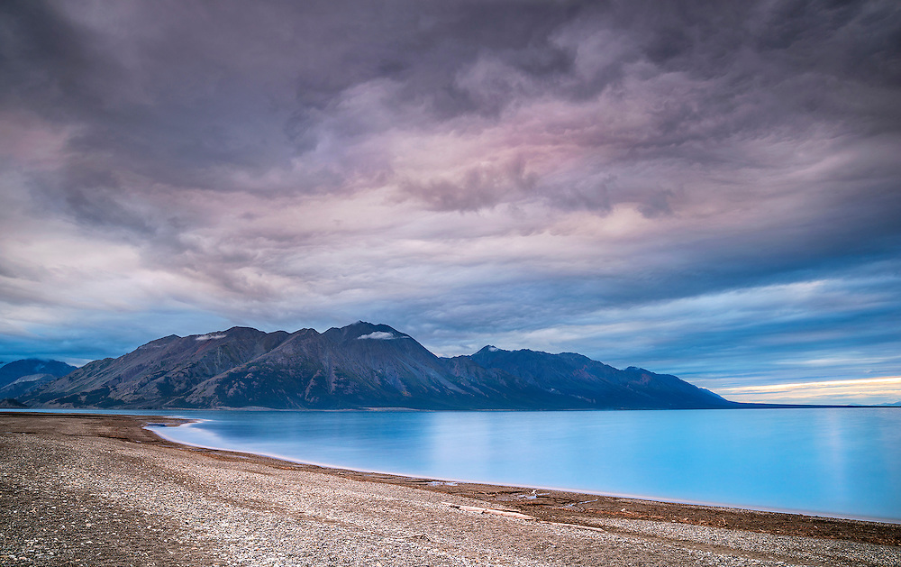 This scene was surreal to witness. The rolling, boiling clouds swept in being pushed by high winds and the lake was blue and clear. Standing on the edge of Kluane Lake, I could see the clouds moving and feel the energy in the air.