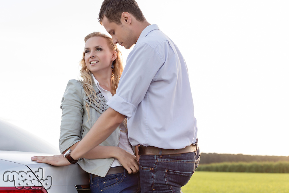 Romantic young couple leaning on back of car at countryside