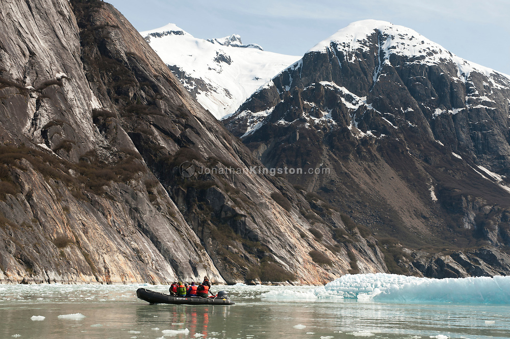 A inflatable boat in a glacial tidewater bay surrounded by icebergs.