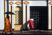 East coast town of Trincomalee. Two Buddhist priests walk past a Hindu Kovil (temple) and while a woman leaves an offering at the Hindu shine.