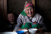 Family members inside a hut insulated with felt, where they live during summer on the high altitude jailoo (pastures), Tien Shan mountains, Kyrgyzstan