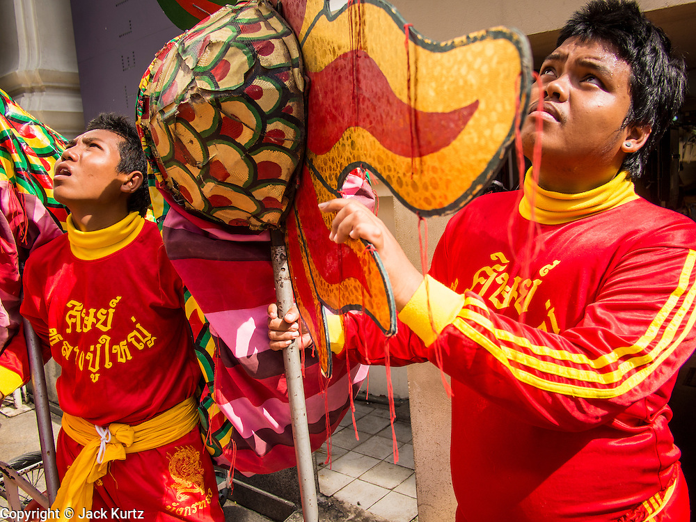17 AUGUST 2013 - BANGKOK, THAILAND:    Members of a Dragon dance troupe watch the acrobats in their troupe perform at Erawan Shrine in Bangkok. The Chinese Dragon Dance began during the Han Dynasty which lasted from 206 BC to 24 AD. In those ancient days it was performed by the people of China specifically to please their ancestors and to insure sufficient rain for a plentiful crop. In this way they hoped to protect against hunger and sickness. Over time the Dragon Dance became a central feature in Chinese celebrations with different colors symbolizing different characteristics or desired features; red for excitement, green for a good harvest, yellow for a solemn empire and gold or silver for prosperity. The Dragon Dance is a well-choreographed event whose difficulty is dependent upon the performers' skill. The length of the dragon indicates just how much luck it will bring in the coming year, but a longer dragon requires more performers with great skill as an error by one can ruin the entire performance. The dragon is typically between 82 and 229 feet long. The head along can weigh as much as 31 pounds. Both strength and skill are both required in performing the Chinese Dragon Dance.        PHOTO BY JACK KURTZ