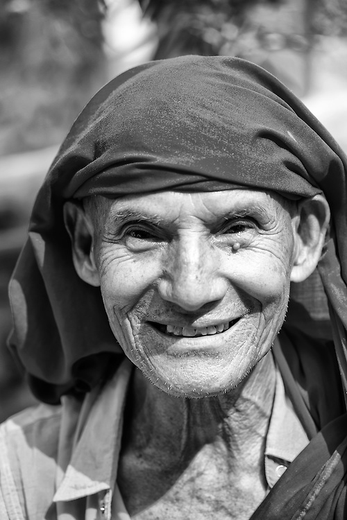 A black and white portrait of an aged buddhist monk from Nepal