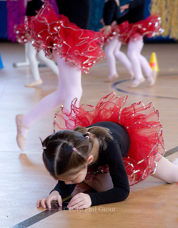 """Photo by Phil Grout..Budding ballerina, 4-year-old Sarah Rupprecht of Eldersburg,.pauses in the performance to explore her reflection in a shiny.electrical plate on the dance floor while the show goes on.featuring the """"Stepping Stars"""" at the Freedom Fitness and Health.Expo."""