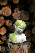 green moss covered bust of young girl with pile of wood in the background