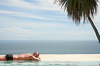 Man sunbathing at edge of pool ocean in background