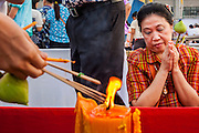 13 APRIL 2014 - BANGKOK, THAILAND:  A woman prays and lights incense during a Songkran ceremony at Bangkok City Hall. Many people go to temples and religious ceremonies to make merit on Songkran. Songkran is celebrated in Thailand as the traditional New Year's Day from 13 to 16 April. Songkran is in the hottest time of the year in Thailand, at the end of the dry season and provides an excuse for people to cool off in friendly water fights that take place throughout the country. Songkran has been a national holiday since 1940, when Thailand moved the first day of the year to January 1.   PHOTO BY JACK KURTZ