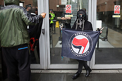 © Licensed to London News Pictures . 02/09/2015 . Manchester , UK . Protesters holding antifascist flags and complaining about a trial involving an anti-fracking protester , outside Manchester Magistrates' Court , as police block the doorway following protesters storming the court this afternoon (Wednesday 2nd September 2015). Photo credit : Joel Goodman/LNP