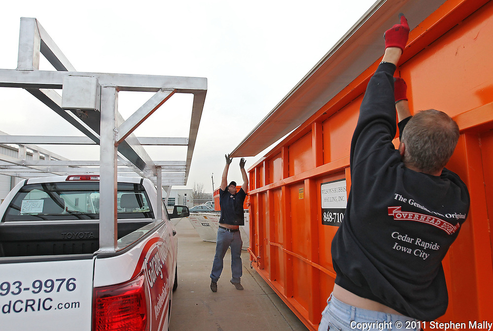 Brent Pettigrew (from left) and Leon Noska, both of Cedar Rapids, toss a section of a garage door into a metal recycling bin at Overhead Door Company, 6515 4th Street SW in Cedar Rapids on Monday afternoon, November 21, 2011. (Stephen Mally/Freelance)