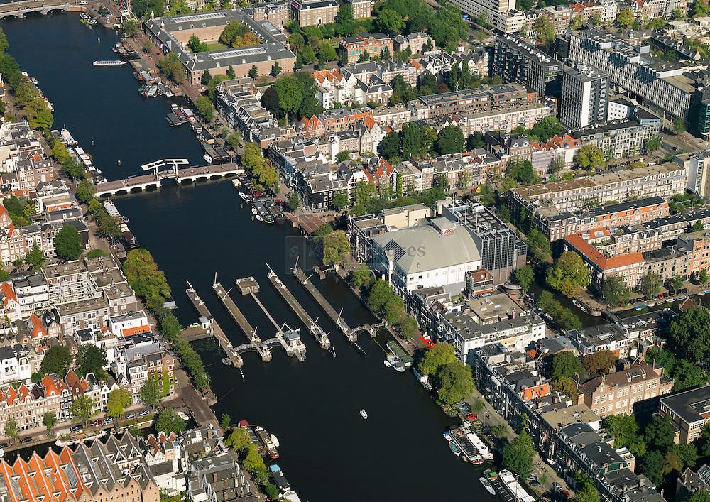 Rivier de Amstel stroomt langs theater Carre met de Amstelsluizen en de magere brug
