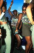 Girls in matching camo gear dancing, Notting Hill Carnival, London, UK, 2000's