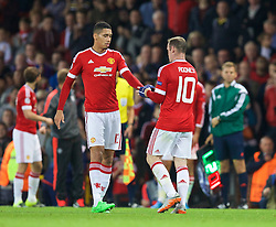 MANCHESTER, ENGLAND - Tuesday, August 18, 2015: Manchester United's captain Wayne Rooney hands the armband to Chris Smalling as he is substituted against Club Brugge during the UEFA Champions League Play-Off Round 1st Leg match at Old Trafford. (Pic by David Rawcliffe/Propaganda)