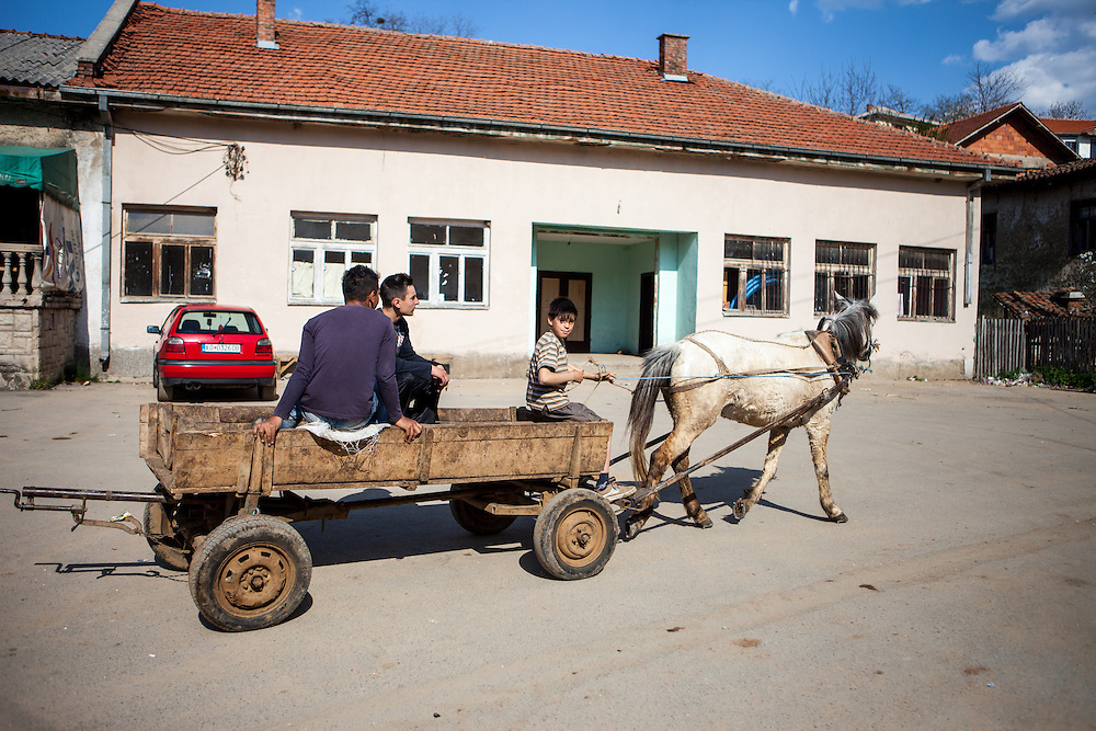 Boys with a horse passing the local grocery store in the city of Crnik. Crnik has almost 90% of unemployment.