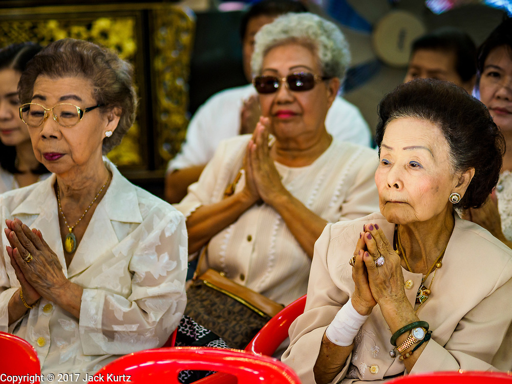 "22 AUGUST 2017 - BANGKOK, THAILAND: Women pray during a ceremony on the first day of Hungry Ghost Month at the Poh Teck Tung Shrine in Bangkok's Chinatown. The seventh lunar month (August - September) is when many Chinese believe Hell's gate will open to allow spirits to roam freely in the human world. Many households and temples hold prayer ceremonies throughout the month-long Hungry Ghost Festival (Phor Thor) to appease the spirits. During the festival, believers will also worship the Tai Su Yeah (King of Hades) in the form of paper effigies which will be ""sent back"" to hell after the effigies are burnt.      PHOTO BY JACK KURTZ"
