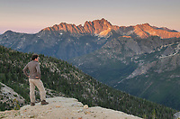 Adult male standing at cliffside viewpoint and gazing at view of Silver star Mountain on ridge above Cutthroat Pass, near Pacific Crest trail. North Cascades Washington