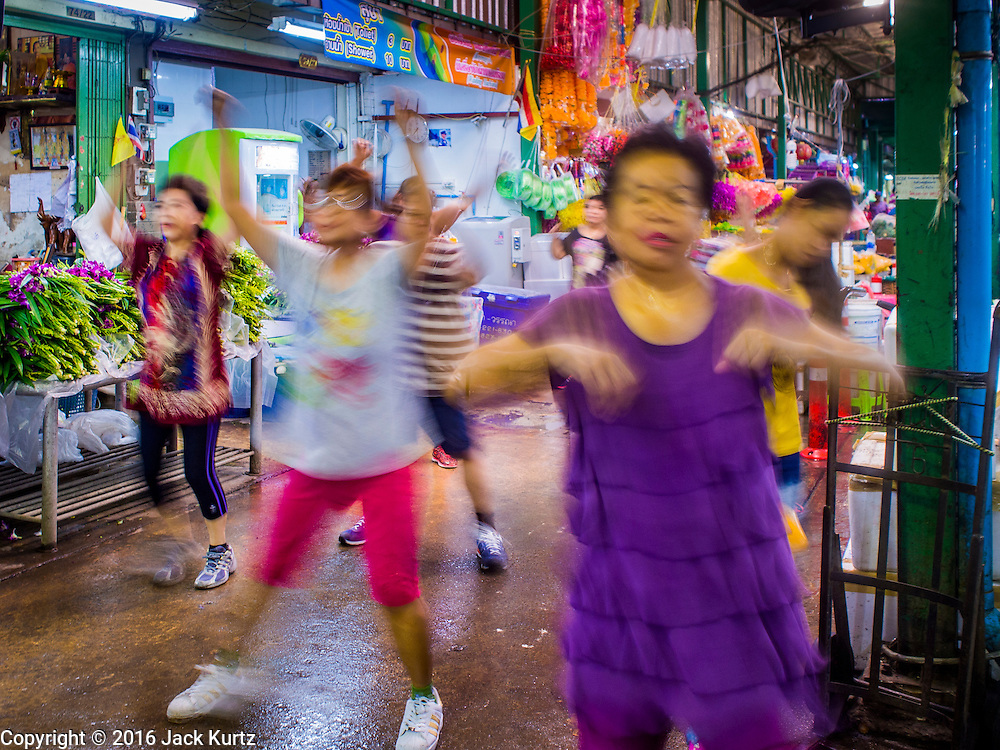 25 AUGUST 2016 - BANGKOK, THAILAND:      Women in an aerobics class in Pak Khlong Talat, better known as the Bangkok Flower Market. Public exercise classes are common throughout Thailand and a part of Thailand's public health program. Most of the participants in the exercise class in the Bangkok flower market are older adults, although the class is open to everyone.       PHOTO BY JACK KURTZ