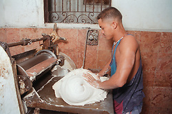 Baker kneading dough to make bread in bakery in Havana; Cuba,