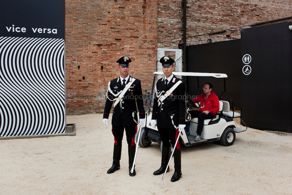 VENICE, ITALY - 30 MAY 2013: Two carabinieri secure the entrance of the Italian Pavillon for its inauguration at the Arsenale in Venice, Italy, on May 30th 2013. <br /> <br /> The Italian Pavilion presents vice versa, an ideal journey through Italian art of today,<br /> an itinerary that tells of identities, history and landscapes - real and imaginary - exploring the complexity and layers that characterize the country's artistic vicissitudes. The Italian Pavillon is curated by Bartolomeo Pietromarchi,<br /> who describes the exhibition as, ?A portrait of recent art, read as an atlas of themes and attitudes in dialogue with the historical legacy and current affairs, with both a local and international dimension. A cross-dialogue of correspondences, derivations and differences between acclaimed maestros and artists of later generations&quot;. The exhibition is divided into seven spaces - six rooms and a garden - that each house<br /> the work of two artists,<br /> who are brought together on the basis of the affinity of their<br /> respective poetics and common interests in themes, ideas and practices.<br /> <br /> The 55th International Art Exhibition of the Venice Biennale takes place in Venice from June 1st to November 24th, 2013 at the Giardini and at the Arsenale as well as in various venues the city. <br /> <br /> Gianni Cipriano for The New York TImes