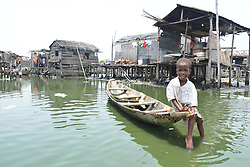 LAGOS, NIGERIA - MARCH 24: Nigerian kid sits over a boat as Police officers demolish unlicensed constructions which were built over lake at the Otodo Gbame slum neighnoorhood in Lagos, Nigeria on March 24, 2017.<br />