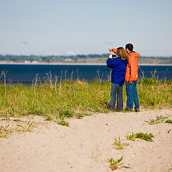 A young couple watches for wildlife on Long Beach in Stratford, Connecticut.  Adjacent to the Great Meadows Unit of McKinney National Wildlife Refuge.