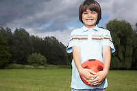 Portrait of boy (7-9) in meadow with football