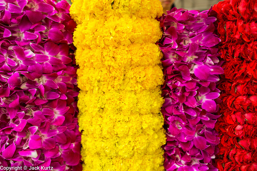 27 SEPTEMBER 2012 - BANGKOK, THAILAND:  Flower garlands for sale at the Erawan Shrine in Bangkok. People buy the garlands as offerings for the shrine. The Erawan Shrine is a Hindu shrine in Bangkok, Thailand, that houses a statue of Phra Phrom, the Thai representation of the Hindu creation god Brahma. A popular tourist attraction, it often features performances by resident Thai dance troupes, who are hired by worshippers in return for seeing their prayers at the shrine answered. The Erawan Shrine was built in 1956 as part of the government-owned Erawan Hotel to eliminate the bad karma believed caused by laying the foundations on the wrong date. The hotel's construction was delayed by a series of mishaps, including cost overruns, injuries to laborers, and the loss of a shipload of Italian marble intended for the building. Furthermore, the Ratchaprasong Intersection had once been used to put criminals on public display. An astrologer advised building the shrine to counter the negative influences. The Brahma statue was designed and built by the Department of Fine Arts and enshrined on 9 November 1956. The hotel's construction thereafter proceeded without further incident. In 1987, the hotel was demolished and the site used for the Grand Hyatt Erawan Hotel.     PHOTO BY JACK KURTZ