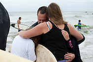 20110911 - Long Beach , NY - Eric Robinson, a member of the Freeport Fire Department, embraces his family after returning from a paddle out in remembrance of 9/11 as part of a beach mass and ecumenical service at National Boulevard Beach.  .Photo by Isabel Slepoy / LI Herald