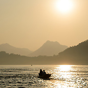 Two men in a small sampan head towards the setting sun in the late afternoon on the Mekong River near Luang Prabang, Laos.