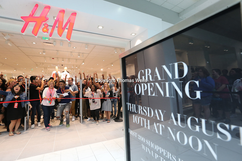 Employees celebrate following the ribbon cutting to officially open the new H&M at The Mall at Barnes Crossing on Thursday.