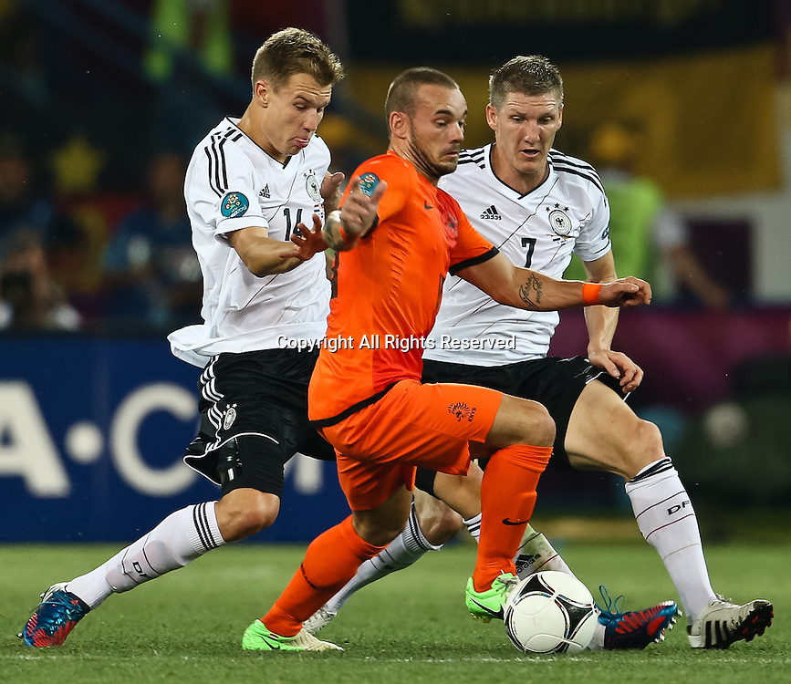 13.06.2012 Ukraine, Kharkiv : Ukraine, Kharkiv.  Netherlands national team player Wesley Sneijder (center) and German national team players Holger Badstuber (L), Bastian Schweinsteiger (R)  in the group stage European Football Championship match between teams of the Netherlands and Germany.