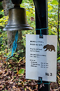 """Ring the bell hard against bears"" sign on preserved fuedal Nakasendo route from Tsumago to Magome, Japan. Tsumago preserves an Edo Period post town on the fuedal Nakasendo route between Kyoto and Edo (present-day Tokyo). To enforce historic ambiance, phone lines and power cables are concealed, and cars are prohibited during daytime. Visitors are encouraged to stay in minshuku and ryokan lodging, and to hike a portion of the trail preserved between Tsumago and Magome villages, via pleasant rural and forest scenery. The Nakasendo, or ""Central Mountain Route"", was one of Five Routes (Gokaido, begun in 1601) which helped the Tokugawa shogunate to stabilize and rule Japan (1600-1868). Tsumago is in Nagano Prefecture, Japan."