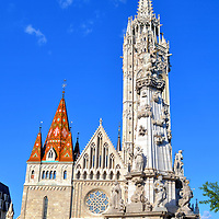Matthias Church in Budapest, Hungary<br /> The Church of Our Lady was built on Castle Hill in the mid-13th century. Over 200 years later, it assumed the name of King Matthias. In 1541 and again in 1686, this Catholic church was plundered by the Turks. In the late 19th century, its original design was lovingly restored by Frigyes Schulek. The diamond pattern roof crowns Béla Tower, named after King Béla IV who founded the church. The tall, white Gothic spire is Matthias Tower. In the foreground where the two women are sitting is Trinity Column. This Baroque creation by Philipp Ungleich has been the centerpiece of Holy Trinity Square since 1713.
