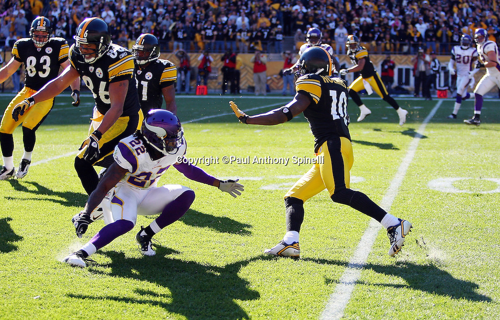 Pittsburgh Steelers wide receiver Santonio Holmes (10) catches a pass at the beginning of the fourth quarter pass while trying to avoid a tackle by Minnesota Vikings cornerback Benny Sapp (22) during the NFL football game, October 25, 2009 in Pittsburgh, Pennsylvania. The Steelers won the game 27-17. (©Paul Anthony Spinelli)