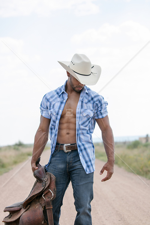 Hot black cowboy with an open shirt holding a saddle on a dirt road