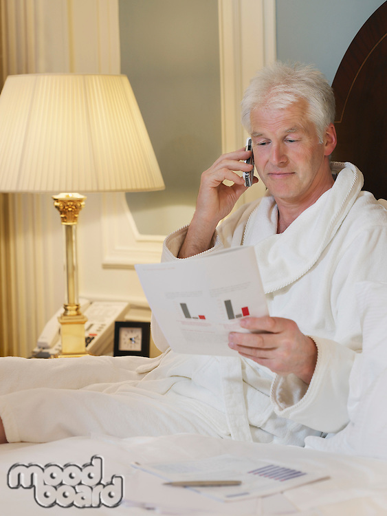 Man sitting in bed using mobile phone