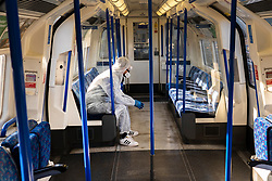 © Licensed to London News Pictures. 22/03/2020. London, UK.  A man wears protective clothing with gloves and goggles to protect himself from the Coronavirus as he travels on the Northern Line in London. Photo credit: João Castellano/LNP