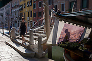 Pedestrians and tourists walk over a canal bridge with shadows on an afternoon sun screen in Dorsoduro, a district of Venice, Italy.