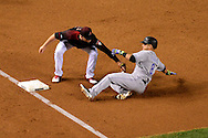 PHOENIX, AZ - APRIL 30:  Gerardo Parra #8 of the Colorado Rockies is tagged out while attempting to steal third base by Brandon Drury #27 of the Arizona Diamondbacks in the third inning at Chase Field on April 30, 2016 in Phoenix, Arizona.  (Photo by Jennifer Stewart/Getty Images)