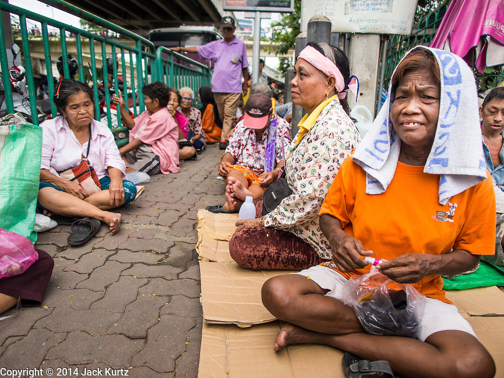 "07 AUGUST 2014 - BANGKOK, THAILAND: People wait for food distribution to start at Pek Leng Keng Mangkorn Khiew Shrine. Thousands of people lined up for food distribution at the Pek Leng Keng Mangkorn Khiew Shrine in the Khlong Toei section of Bangkok Thursday. Khlong Toei is one of the poorest sections of Bangkok. The seventh month of the Chinese Lunar calendar is called ""Ghost Month"" during which ghosts and spirits, including those of the deceased ancestors, come out from the lower realm. It is common for Chinese people to make merit during the month by burning ""hell money"" and presenting food to the ghosts. At Chinese temples in Thailand, it is also customary to give food to the poorer people in the community.     PHOTO BY JACK KURTZ"