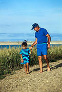 Grandfather walking with granddaughter along the beach. Cape Cod