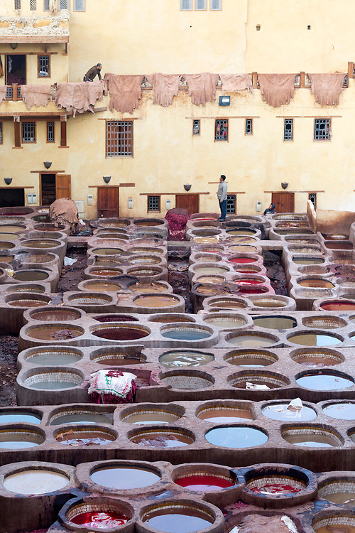FEZ, MOROCCO - 1st DECEMBER 2016 - Workers dye animal hides in the tannery vats at the Chouwara Tannery, old Fez Medina, Middle Atlas Mountains, Morocco.