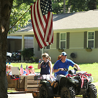 Joyner residents pass an American Flag as they ride along Chester Street in the Joyner Neighborhood Fourth of July Parade  Wednesday morning in Tupelo.