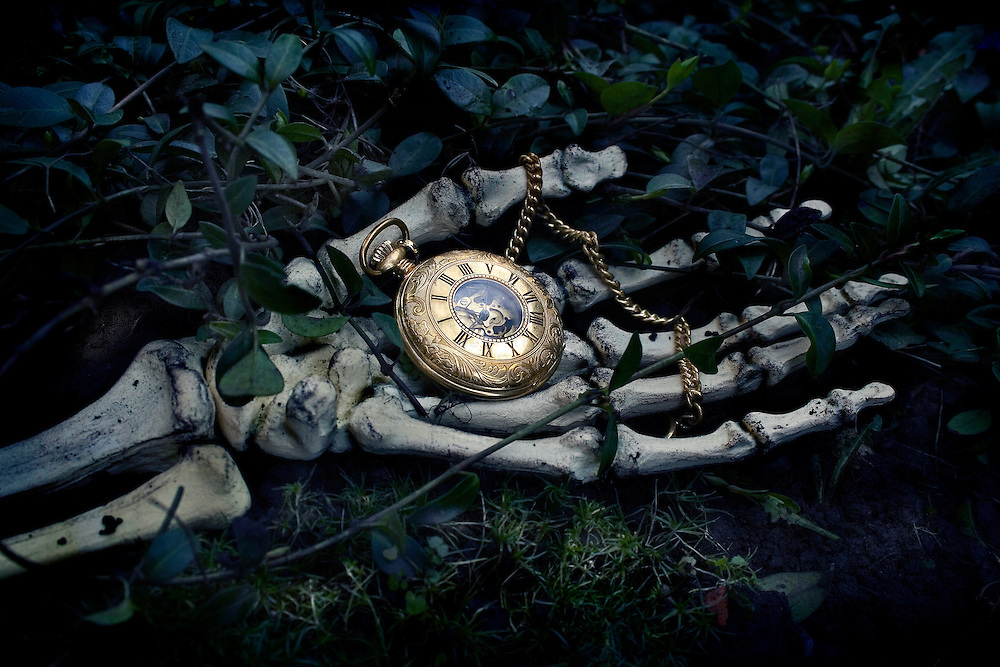 Skeleton hand holding ornate pocket watch with chain