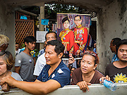 03 SEPTEMBER 2016 - BANGKOK, THAILAND:  Residents of Pom Mahakan community hold up a portrait of the King and Queen of Thailand while they blockade a gate into their community. Hundreds of people from the Pom Mahakan community and other communities in Bangkok barricaded themselves in the Pom Mahakan Fort to prevent Bangkok officials from tearing down the homes in the community Saturday. The city had issued eviction notices and said they would reclaim the land in the historic fort from the community. People prevented the city workers from getting into the fort. After negotiations with community leaders, Bangkok officials were allowed to tear down 12 homes that had either been abandoned or whose owners had agreed to move. The remaining 44 families who live in the fort have vowed to stay.     PHOTO BY JACK KURTZ