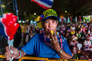 07 MAY 2014 - BANGKOK, THAILAND:  A woman blows a whistle in support of Suthep Thaugsuban in Lumpini Park in Bangkok. Thousands of members of the People's Democratic Reform Committee (PDRC), an anti-government organization led by Suthep, gathered at their protest site in Lumpini Park in Bangkok to  celebrate the ruling by the Thai Constitutional Court today that forced the ouster of Prime Minister Yingluck Shinawatra. This is the third consecutive popularly elected Thai government ousted by the courts. The Red Shirts, who support the government, are coming to Bangkok to protest court ruling later in the week.   PHOTO BY JACK KURTZ