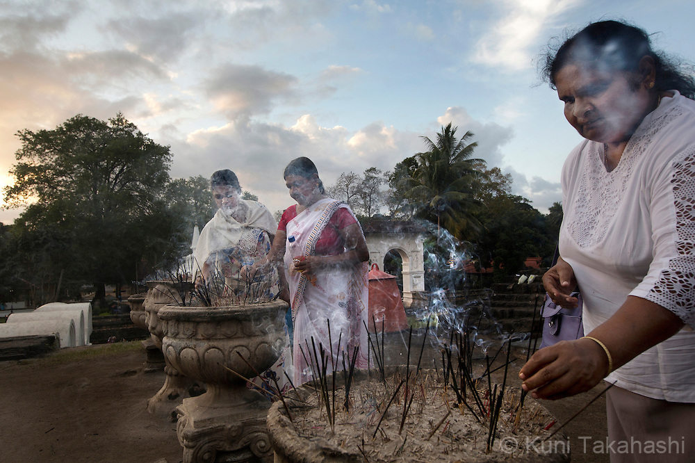 Women pray at Sri Dalada Maligawa, or Temple of the Tooth Relic, in Srilanka on January 4, 2016. The temple houses the one of the two surviving relic of Buddha's tooth and attracts many tourists and Buddhist pilgrims. <br /> (Photo by Kuni Takahashi)