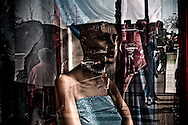 Window reflection with mannequin on display at Chinese clothing store, Tronto, Canada